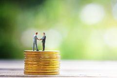 Miniature businessman handshak on gold coin Stock Photo