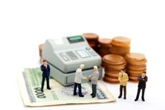 Miniature businessman handshake with coin stack and cash machine stock images