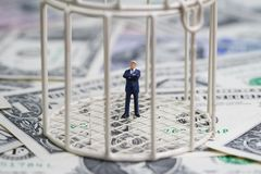 Miniature businessman inside birdcage on pile of dollar banknote. Miniature businessman ine birdcage on pile of dollar banknotes metaphor of ine the box thinking Royalty Free Stock Photos
