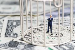 Miniature businessman inside birdcage on pile of dollar banknote. S metaphor of limited thinking or money trap Royalty Free Stock Photo