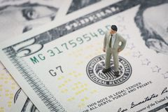 Miniature businessman leader standing and thinking on US Federal. Reserve emblem on five dollars banknote as FED consider interest rate hike, economics and stock photos