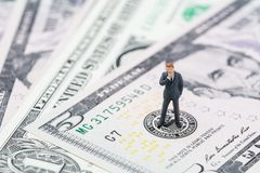 Miniature businessman leader standing and thinking on US Federal. Reserve emblem on five dollars banknote as FED consider interest rate hike, economics and stock photo