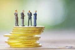 Miniature businessman meeting on gold coin Stock Photos