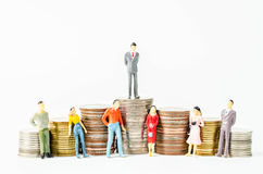 Miniature businessman and people on many stack of coins. Royalty Free Stock Photos