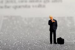 Miniature of a businessman reading a newspaper Royalty Free Stock Photo