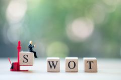 Miniature businessman sitting on wood letters making SWOT analysis text royalty free stock photo