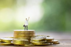 Miniature businessman standing on gold coin Royalty Free Stock Image