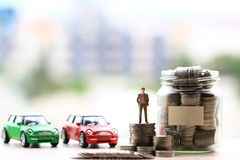 Miniature businessman standing on stack of coins money on city background, Saving money for car, Finance and car loan, Investment royalty free stock images