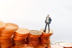 Miniature businessman standing on step of coin money. Royalty Free Stock Image