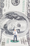 Miniature businessman standing on US dollar. Royalty Free Stock Photos