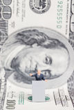 Miniature businessman standing on US dollar. Stock Photo