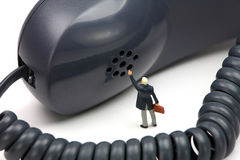 Miniature businessman stands in front of a phone Stock Images