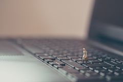 Miniature businessman walking on the laptop Stock Image