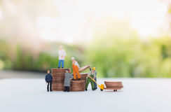 Miniature businessman and  worker standing on the coins and carr Royalty Free Stock Photo