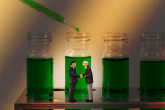 Miniature businessmen with chemical tube on background Stock Photography