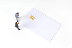 Miniature businessmen discuss on blank credit card Royalty Free Stock Image