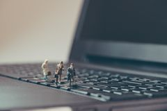 Miniature businessmen walking over the laptop Royalty Free Stock Photography