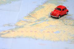 Miniature car driving on a map of Newfoundland Canada. Miniature red toy car driving on a map of Newfoundland Canada stock images