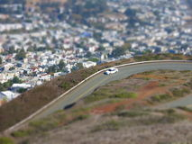 Miniature car effect road above homes. Tilt shift effect showing car on road in the hills near the city of Twin Peaks, San Francisco, California, USA Stock Images