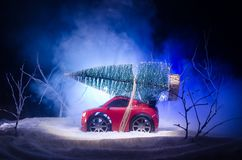 Miniature car with fir tree on Snowy Winter Fores, or toy car carrying a christmas tree and at night time Royalty Free Stock Image