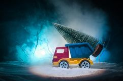 Miniature car with fir tree on Snowy Winter Fores, or toy car carrying a christmas tree and at night time Royalty Free Stock Images