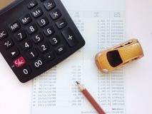 Miniature car model, calculator, and saving account book or financial statement on office desk table. Business, finance, saving money, banking or car loan Stock Photos