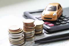 Miniature car model, coins stack, calculator and saving account book or financial statement on office desk table. Business, finance, saving money or car loan Royalty Free Stock Photography