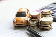 Miniature car model, coins stack, calculator and saving account book or financial statement on office desk table Royalty Free Stock Photos