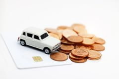 Miniature car model on credit card with coins. Concept of money, finance and car loan. stock images