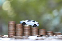 Miniature car model on growing stack of coins money on nature green background, Saving money for car, Finance and car loan,. Investment and business concept royalty free stock photography