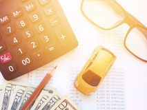 Miniature car model, pencil, calculator, eyeglasses, money and savings account passbook or financial statement on white background Stock Photo
