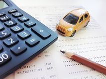 Miniature car model, pencil, calculator and savings account passbook or financial statement on white background Stock Images