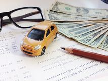 Miniature car model, pencil, eyeglasses, money and savings account passbook or financial statement on white background Royalty Free Stock Photography