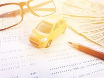 Miniature car model, pencil, eyeglasses, money and savings account passbook or financial statement on white background Royalty Free Stock Image