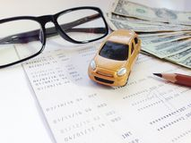 Miniature car model, pencil, eyeglasses, money and savings account passbook or financial statement on white background Royalty Free Stock Photos