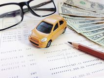 Miniature car model, pencil, eyeglasses, money and savings account passbook or financial statement on white background Stock Photography