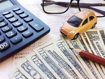 Miniature car model, pencil, money, calculator, eyeglasses and savings account passbook or financial statement on white background Stock Photos