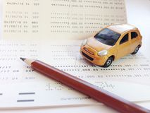 Miniature car model, pencil and savings account passbook or financial statement on white background Stock Image