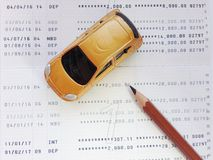 Miniature car model, pencil and savings account passbook or financial statement on white background Stock Photography