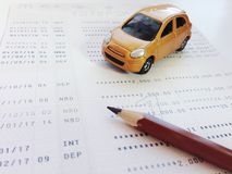 Miniature car model, pencil and savings account passbook or financial statement on white background. Business, finance, savings, banking or car loan concept Stock Photo