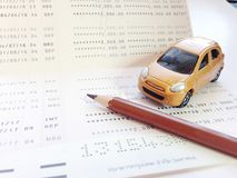 Miniature car model, pencil and savings account passbook or financial statement on white background Royalty Free Stock Photo