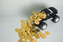 Miniature car pickup truck with stacks of coins on grey backgrou. Black colour of miniature car pickup truck with stacks of coins on grey background with copy Stock Photo