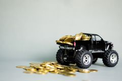 Miniature car pickup truck with stacks of coins on grey backgrou. Black colour of miniature car pickup truck with stacks of coins on grey background with copy Stock Image