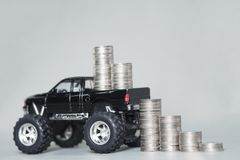 Miniature car pickup truck with stacks of coins on grey backgrou. Black colour of miniature car pickup truck with stacks of coins on grey background with copy Stock Photos