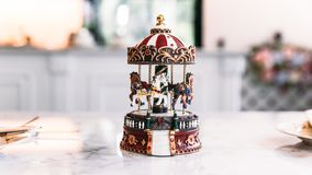 Miniature Carousel Toy over white marble top table with blur background.  royalty free stock image
