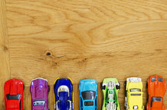 Miniature cars lined up on a wooden floor Stock Images