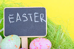Miniature chalkboard with easter eggs Stock Images