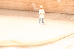 Miniature chef pastry E. Miniature chef standing on a block of puff pastry with rolling pin stock photography
