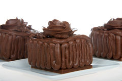 Miniature chocolate cupcake cakes on white plate, chocolate roses Royalty Free Stock Image