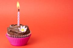 Miniature chocolate cupcake with candle Stock Image